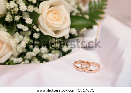 Two wedding rings lays on brides dress behind her bouquet.