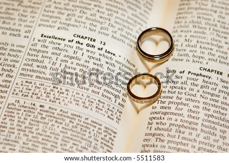 stock photo Two wedding rings on a bible open to Corinthians Chapter 13