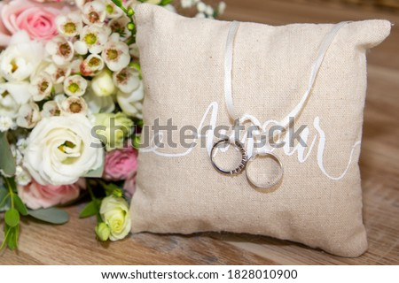 Photo of  two wedding rings on brown natural pillow with ribbon and amour love text and flowers bouquet