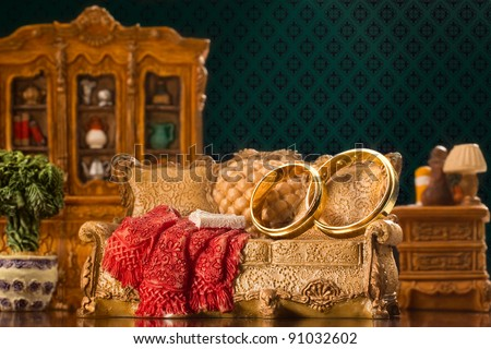 Two wedding rings on couch in antiquarian living room