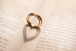Two wedding rings on the book cast shadows in the form of hearts. Valentine's Day. Romance.