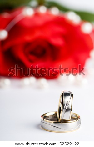 two wedding rings with a pearl necklace and a red rose in the background