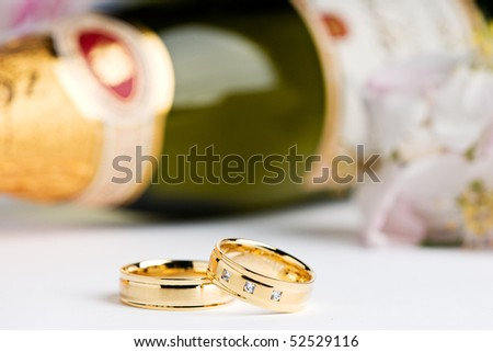 two wedding rings with flowers and a champagne bottle in the background