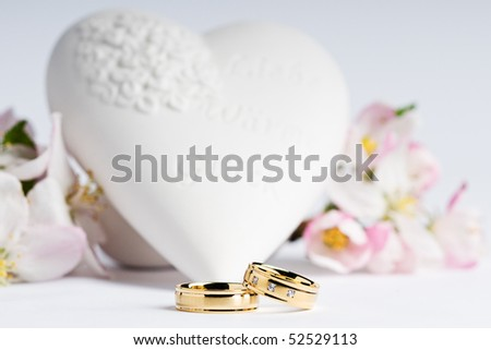 stock photo two wedding rings with flowers and a heart in the background