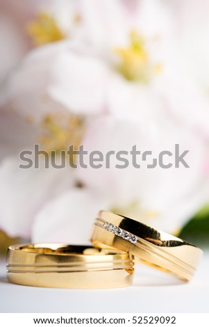 stock photo two wedding rings with flowers in the background