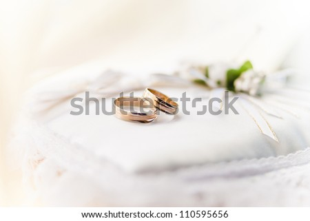 Two wedding rings with white bow in the background.
