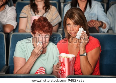 Two weeping women in the audience with tissue paper