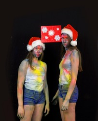 Two weird teenage girls wear Santa Claus hats at  Christmas time. Their clothes and faces are filthy  from power paint. They both have boring expressions  on their faces.