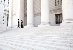 Two well dressed professionals in discussion on the exterior steps of a courthouse. Could be lawyers, business people etc.