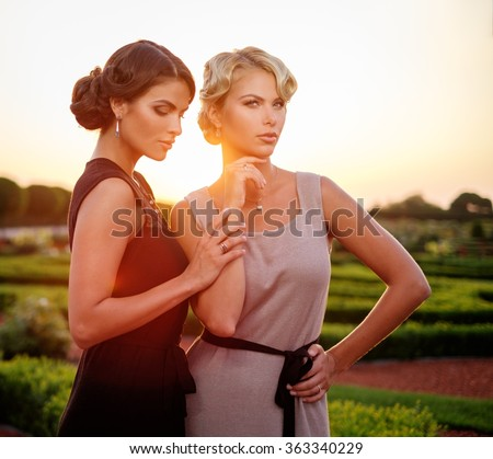 Two well-dressed woman in a beautiful park. #363340229