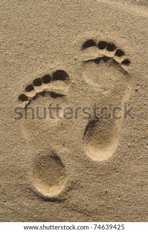 Two well-shaped human footprints in the sand - stock photo