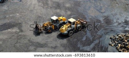 Two wheel loader machines with front buckets passing each other, crossing in opposite directions during earth moving works in a construction site, mine or stone pit / quarry.