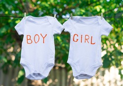 two white baby bodysuits with text boy and text girl hanging on a clothesline on summer background. Gender: boy, girl or twins?