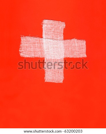 Two white bandages forming a cross on red background - stock photo