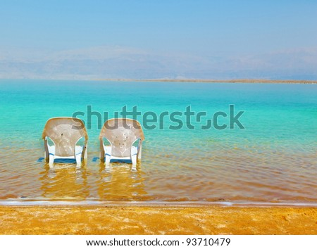 Two white beach chairs stand near the water at the beach. Dead Sea, Israel
