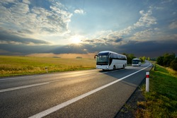 Two white buses traveling on the asphalt road in rural landscape at sunset with dramatic clouds