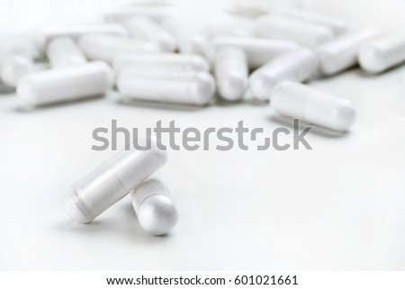 Two white capsules and heap of capsules on white background. High resolution product. Health care concept