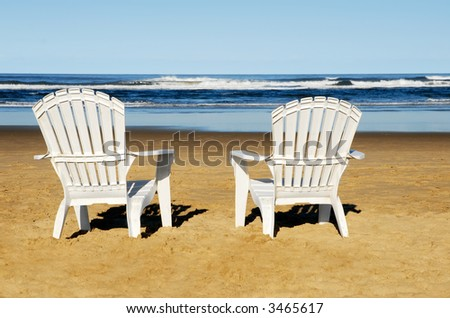 Two white chairs on the beach