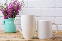 Two white coffee and cappuccino mug mockup with maroon purple field flowers in polka dot mint green pitcher vase.  Empty mug mock up for design promotion.