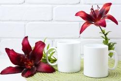 Two white coffee  mug mockup with couple of dark burgundy lily.  Empty mug mock up for design promotion.