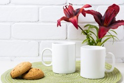 Two white coffee  mug mockup with dark burgundy lily and cookie.  Empty mug mock up for design promotion.