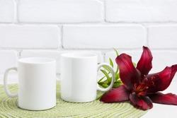 Two white coffee mug mockup with dark burgundy lily.  Empty mug mock up for design promotion.