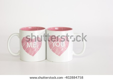 Two white coffee mugs with a heart logo pushed close together spelling 'me you'. Isolated against a pure white background #402884758