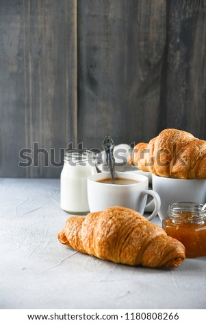 two white cups of coffee with milk, two croissants and jam in a glass jar on a wooden table, Breakfast in European style, selective focus and copy space #1180808266