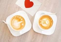 Two white cups of tasty cappucino and valentine letter with heart. Top view. Romantic meeting concept. Wood texture table background.