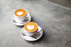 Two white cups of tasty cappucino with love art latte. Valentine's concept. Concrete grey backdrop.