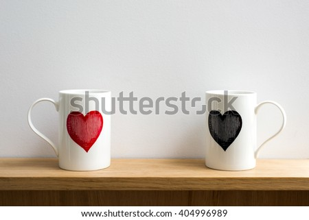 Two white cups on a shelf with red and black heart printed #404996989