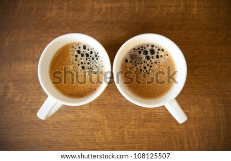 Two white cups with espresso on wood table