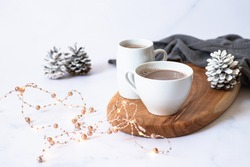 Two white cups with hot chocolate or cocoa drink on a wooden board on a light marble background with festive winter decorations. Winter mood. Frontal view. Copy space. Selective focus