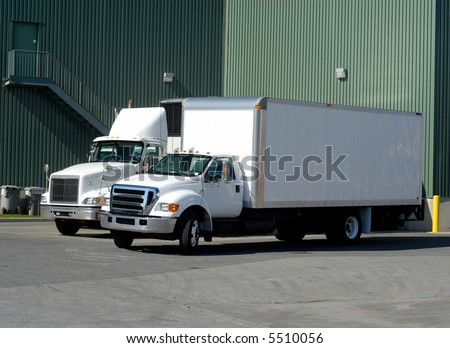 Two White Delivery Trucks Backed Up to A Warehouse Building #5510056