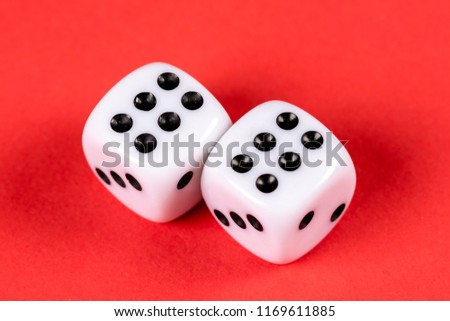 Stock Photo Two white dices against a red background.