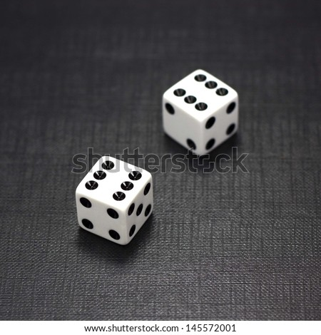 Two white dices on a black background