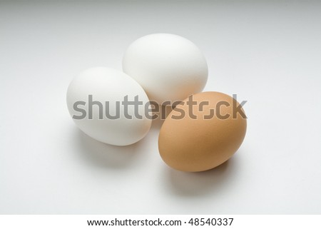 Two white eggs and one brown egg on white - stock photo