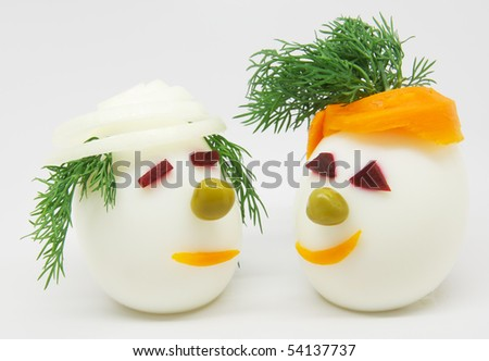Two white eggs decorated with dill, onion and carrots on white background
