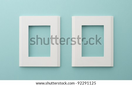 two white frames on the blue wall