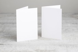 Two white greeting cards mockup, standing upright on a white wooden desk. Blank, closed cards template.