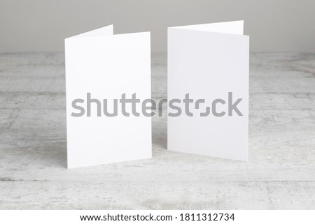 Two white greeting cards mockup, standing upright on a white wooden desk. Blank, closed cards template.  ストックフォト ©