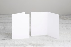 Two white greeting cards mockup, standing upright on a white wooden desk. Blank, open and closed cards template.