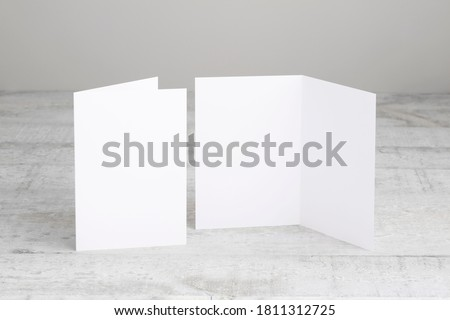 Two white greeting cards mockup, standing upright on a white wooden desk. Blank, open and closed cards template.  ストックフォト ©