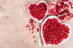 Two white heart shaped plates full of fresh juicy pomegranate seeds, little spoon, whole fruit and ripe one on wooden background.