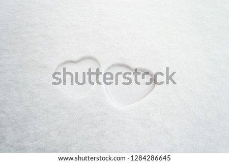 Two white hearts in snow. Minimalist Valentine's Day concept with outlines of two hearts in the snow. Mother's Day and Women's Day theme.