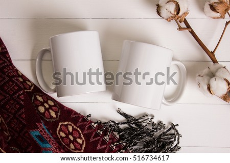 Two white mugs, pair of cups, Mockup. Cozy atmosphere, wooden background, cotton and wool decorations for winter gifts. #516734617