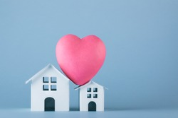 Two white origami houses with big pink heart on the roof on the blue background. Family story in symbols