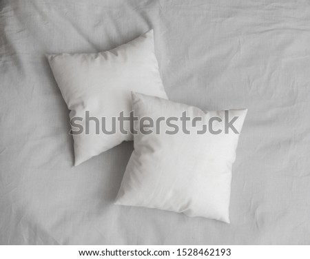 Two white pillows on the bed. White pillows on the bed sheet. Top view.