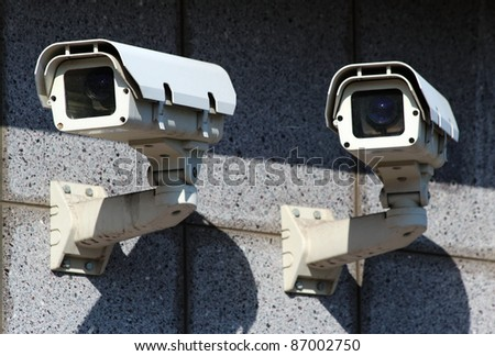 two white security CCTV cameras  on the wall
