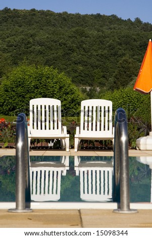 Two white sunloungers reflected in a blue swimming pool, next to an orange umbrella
